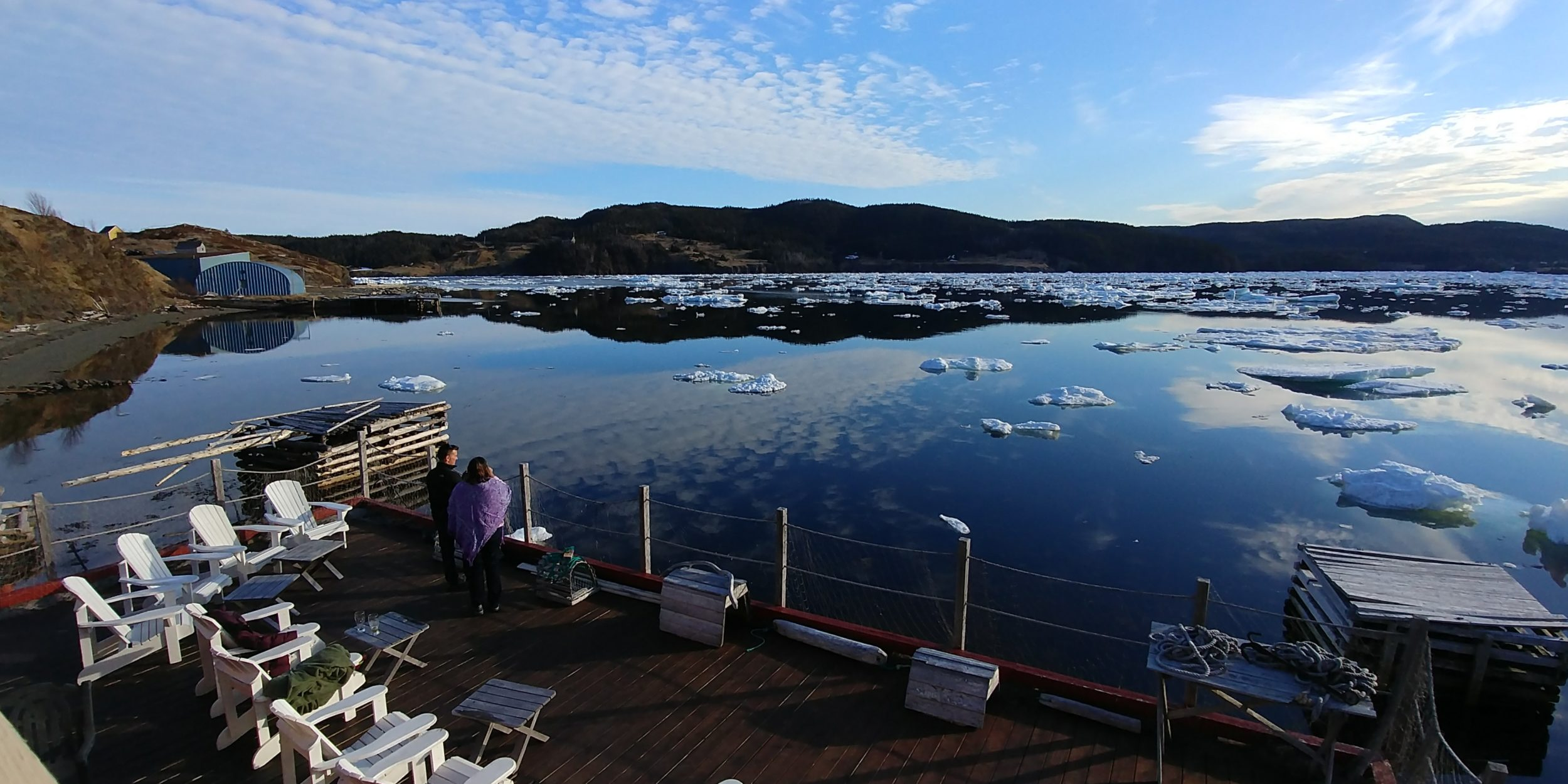 White deck chairs overlook an icy cove in Trinity
