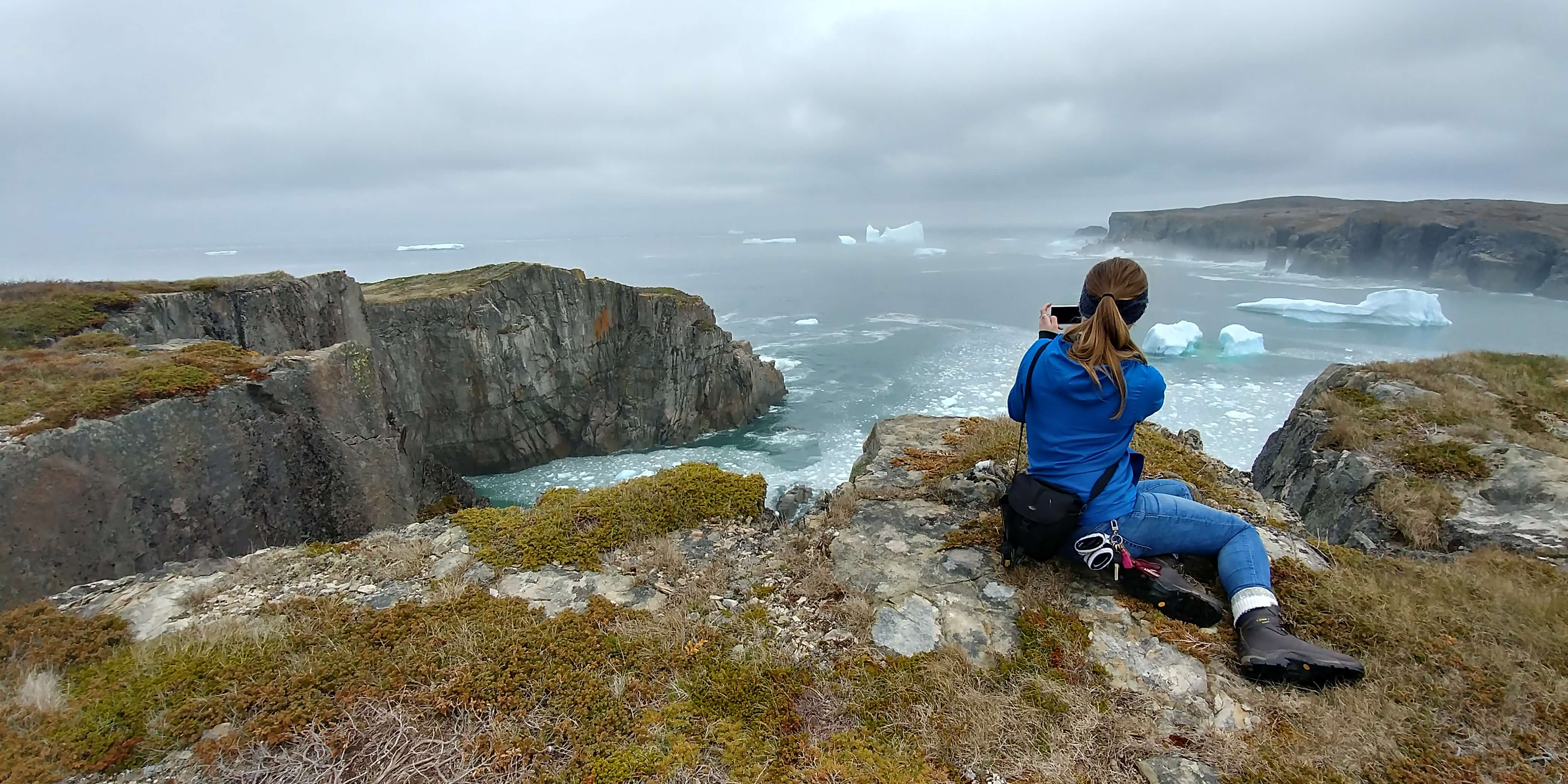 a woman takes a photo of cliffs and icebergs from the Klondike Trail