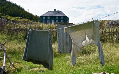 A laundry line is hung with clothing from the 19th century with a square green house in the background
