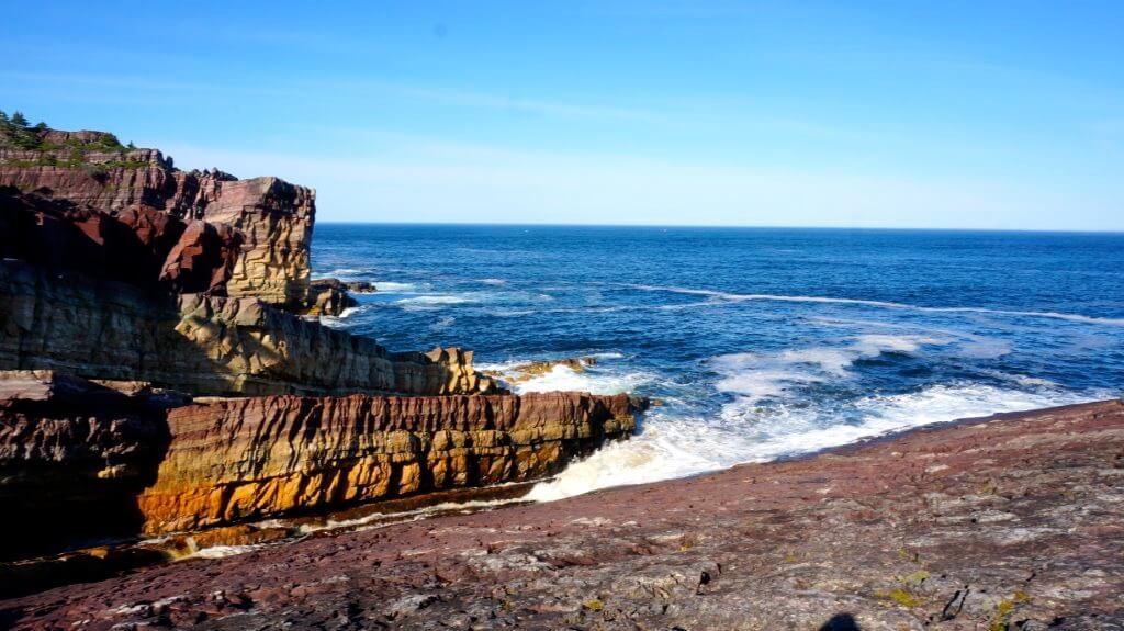 Multi-coloured cliffs jut into a blue ocean