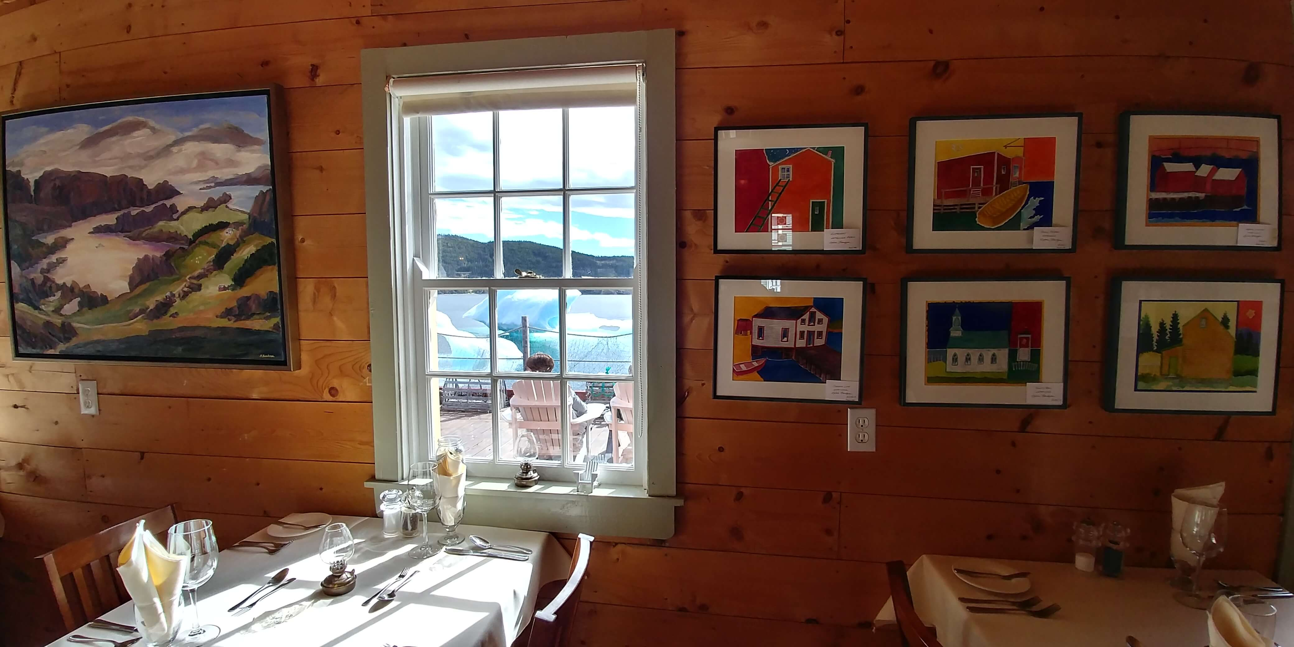 Artwork is displayed on wooden walls adjacent to a window in a dining room