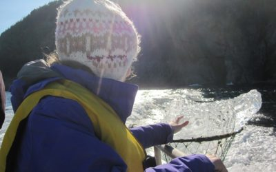 A young passenger touches a chunk of iceberg