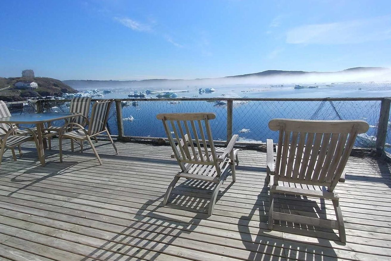 wooden deck chairs on a large wooden deck overlook Trinity Harbour which is full of chunks of sea ice. The cliffs of Skerwink hide behind the fog in the distance
