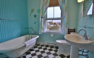 Clawfoot bathtub, checkered floor, toilet and pedestal sink with a window overlooking the town