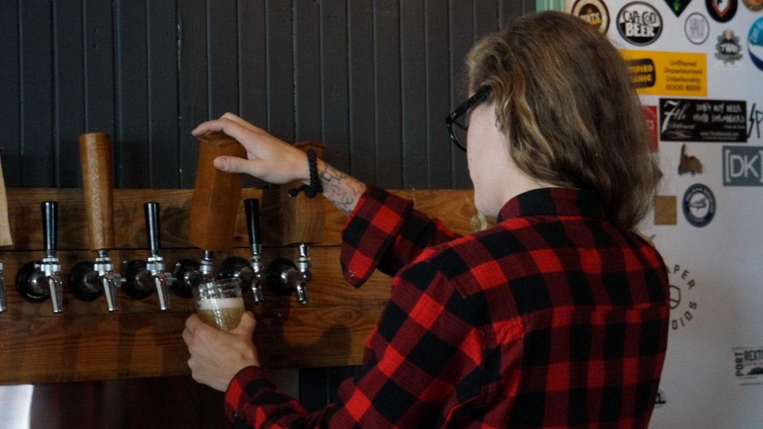 A girl in a plaid shirt pulls a pint of beer
