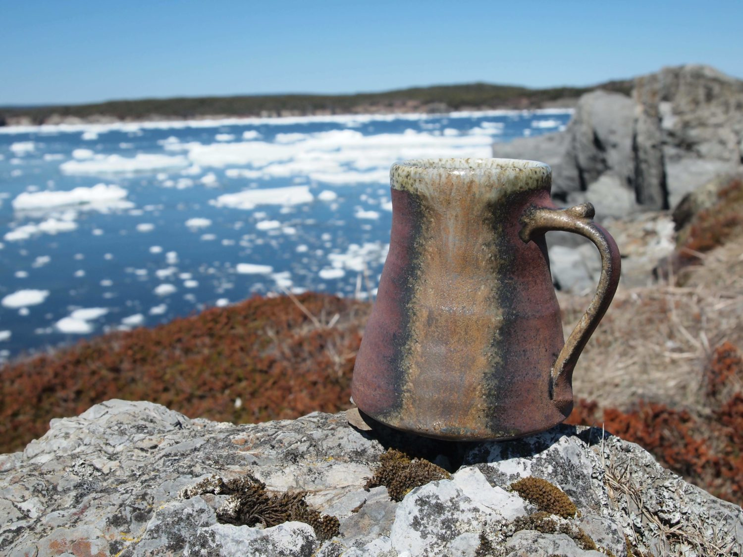 A clay mug sits on a rocky coastline with pack ice in the background