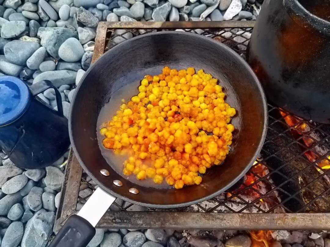 Colourful yellow bakeapples are browned in a frying pan on a rocky beach in Newfoundland