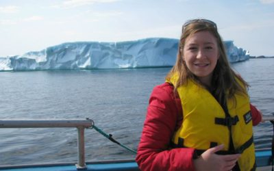 A passanger poses in front of an iceberg while on Rugged Beauty Boat Tour