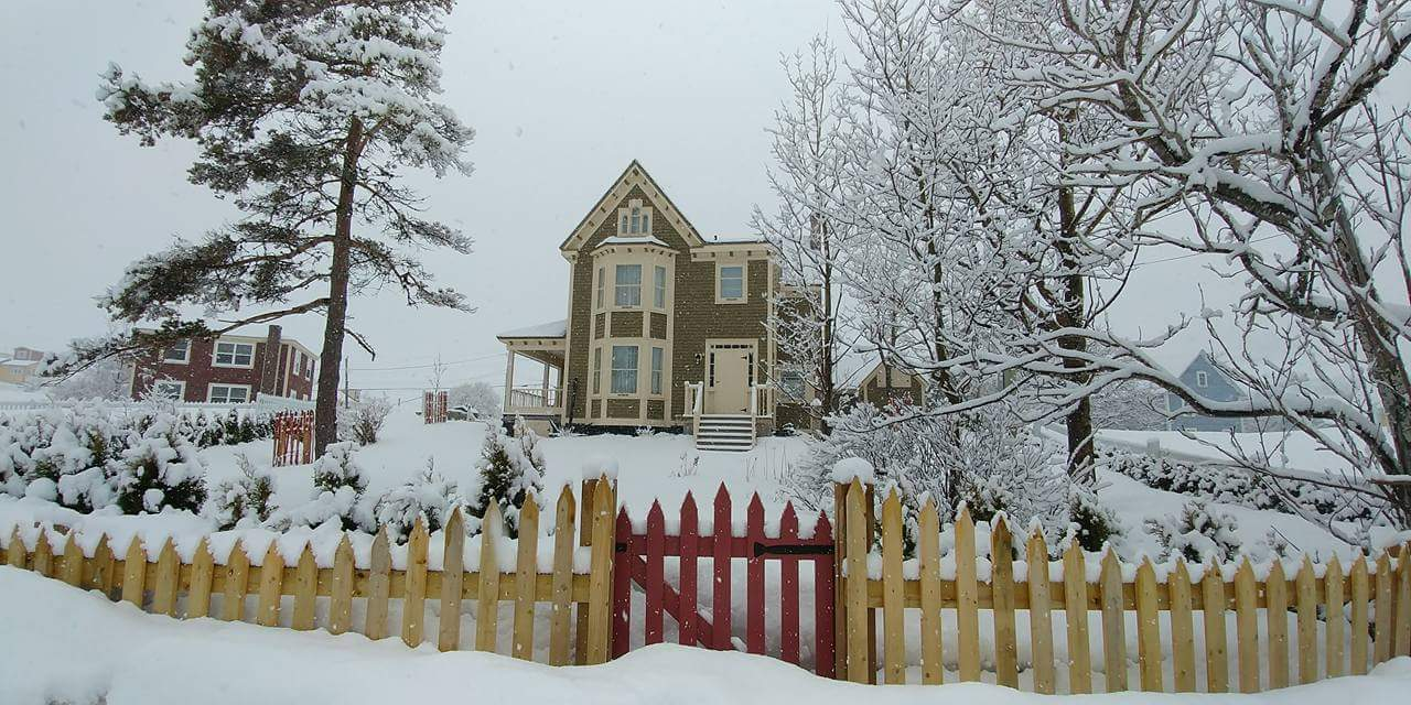 A house with picket fence after the snow