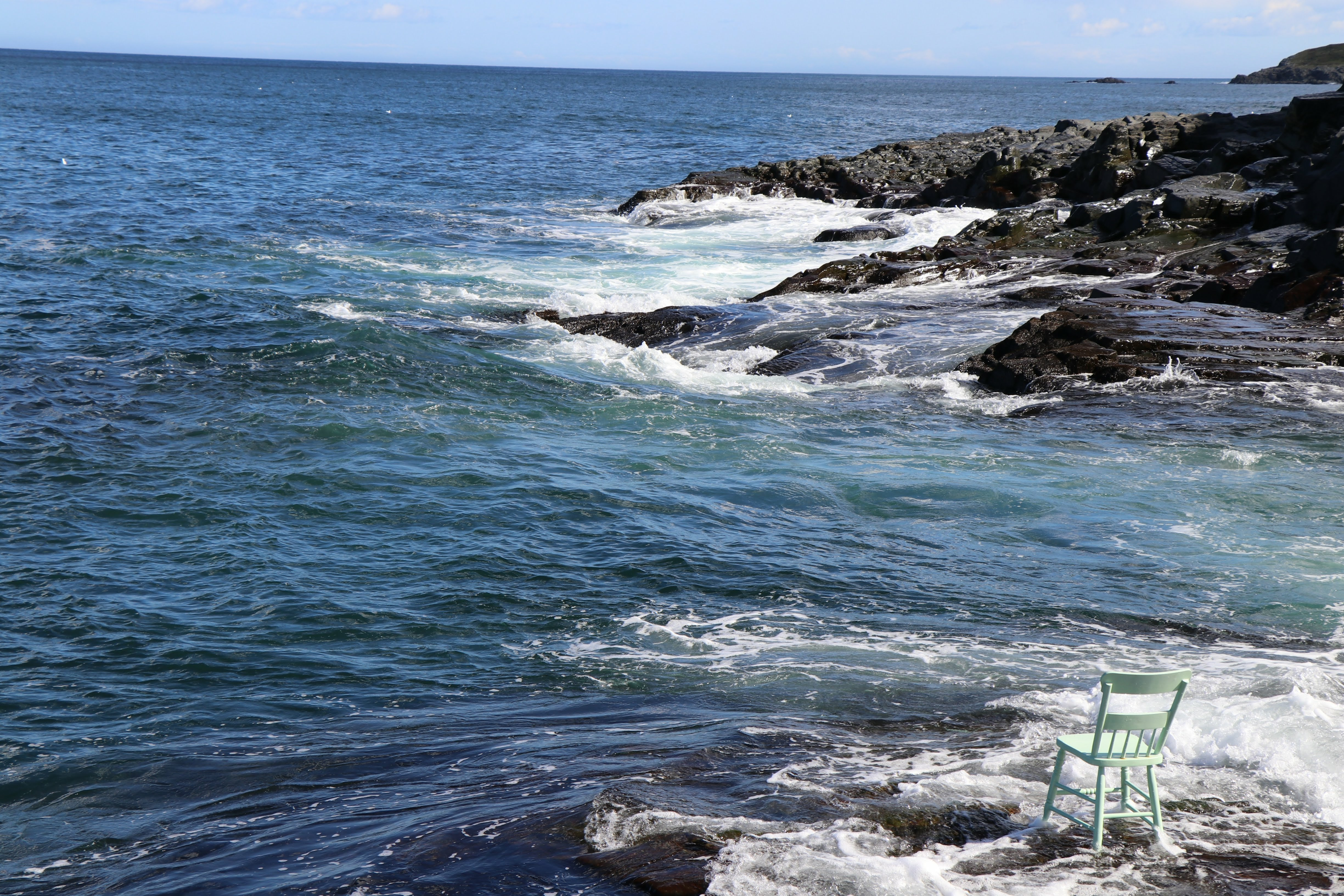 A chair is fastened to the rocks being pummeled by the unforgiving Atlantic waves