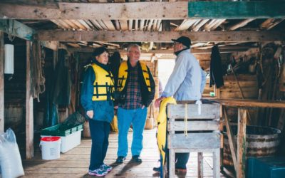 2 visitors chat with a local in a fishing stage